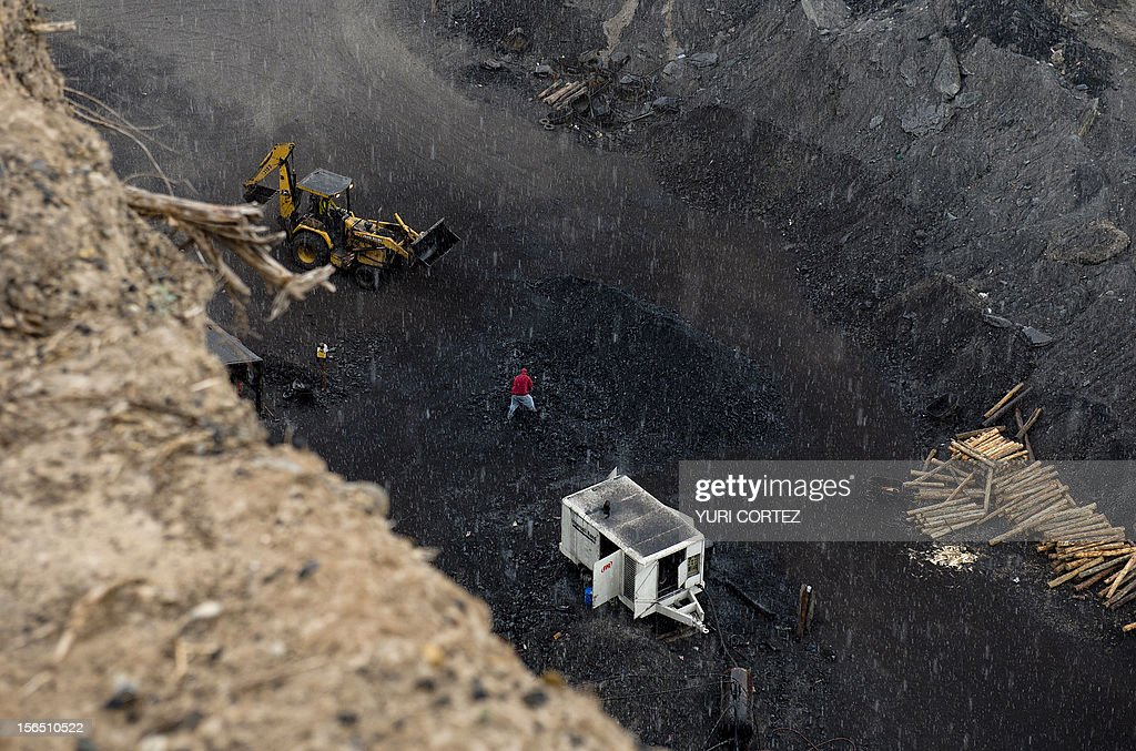 A miner works near a bulldozer in an opencast coal mine in Agujita, Coahuila State in Mexico on November 13, 2012. According to the Mining Chamber of Mexico, the country produces annually 15 million tons of coal, with an average annual production worth USD 3,800 million, representing 1.6% of the country's Gross Domestic Product (GDP) . The bulk of the coal is used for power generation and steel production. Recent press reports affirm that drugs cartel are involved in the coal-related activities.