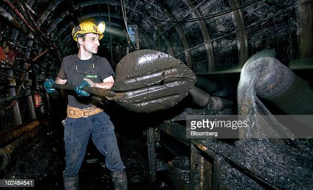 A miner works underground to move loose coal onto a conveyor belt at the Tauron Polska Energia SA coal mine in Jaworzno Poland on Friday June 25 2010...