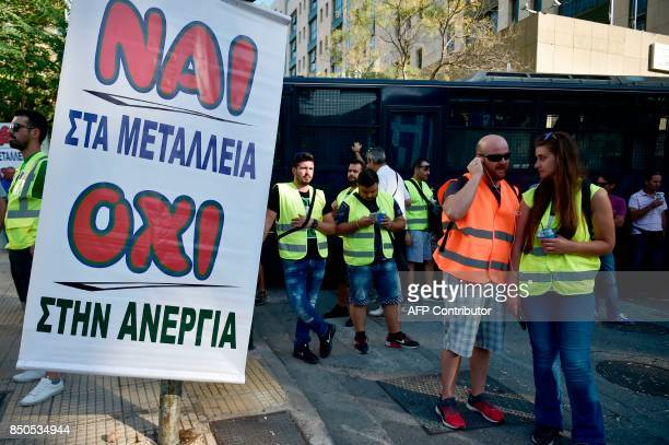 Miners and workers from the Canada's Eldorado Gold mine in northern Greece stand by a banner reading 'yes to mines no to unemployment' during their...