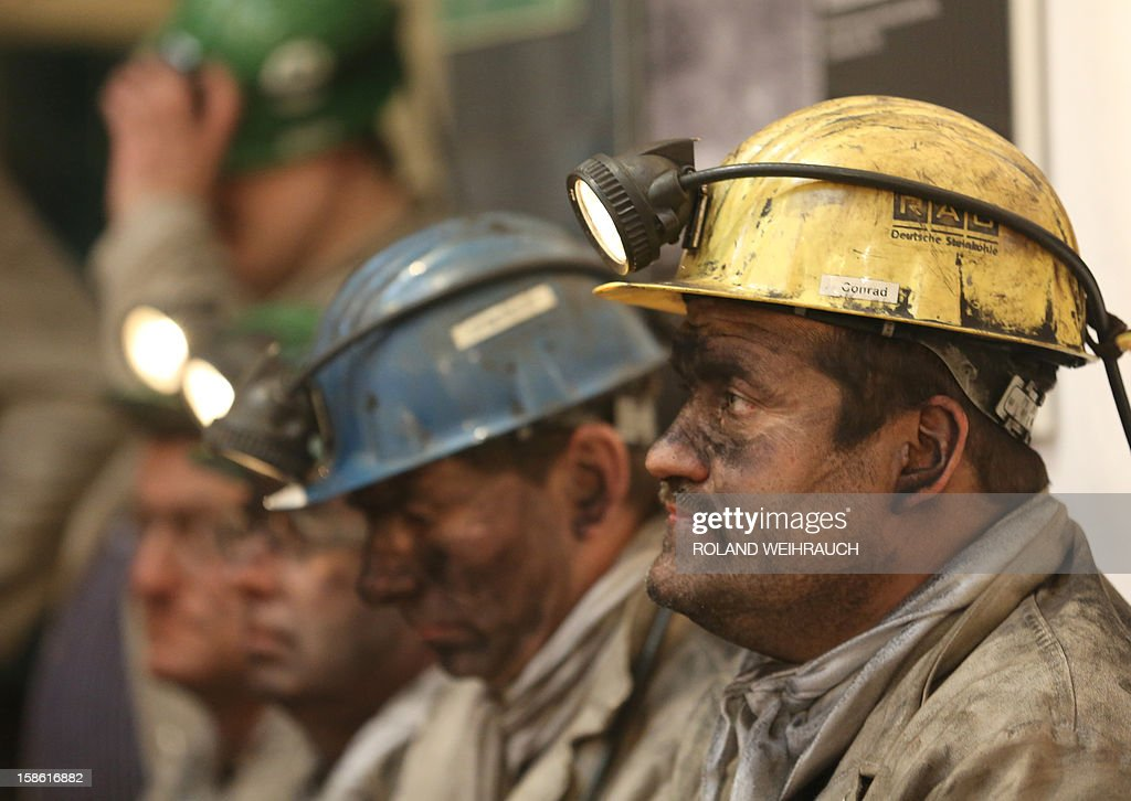 Miners attend the closing ceremony after the very last mining shift at Mine West in Kamp-Lintfort, western Germany, on December 21, 2012. The mine will be shut down after being active for around 100 years. AFP PHOTO / ROLAND WEIHRAUCH GERMANY OUT
