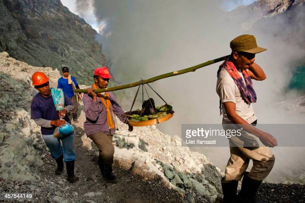 Miners carry a goats head for burial in the crater as part of an annual offering ceremony on the Ijen volcano on December 17 2013 in Banyuwangi...