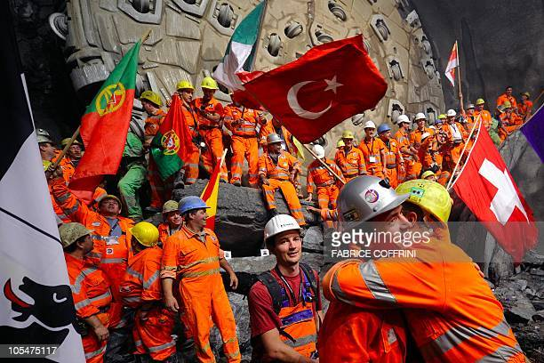 Miners celebrate after a giant drilling machine completed the world's longest tunnel beneath the Swiss Alps during a ceremony on October 15 30...