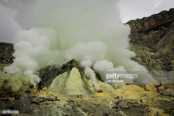 Miners extracts sulphur from pipe at the flow crater during an annual offering ceremony on the Ijen volcano on December 17 2013 in Banyuwangi...