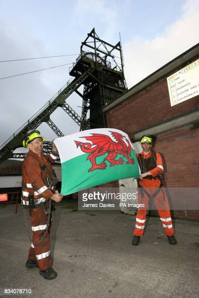 Miners Garry Cutland and Billy Teague loft the Welsh Flag as they finish their last shift at Tower Colliery at Hirwaun Mid Glamorgan Wales