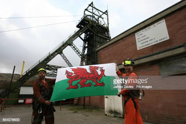 Miners Garry Cutland and Billy Teague loft the Welsh Flag as they finish their last shift at the Tower Colliery at Hirwaun Mid Glamorgan Wales