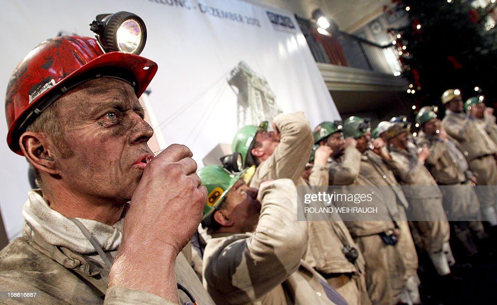 Miners have a schnaps during the closing ceremony after the very last mining shift at Mine West in Kamp-Lintfort, western Germany, on December 21, 2012. The mine will be shut down after being active for around 100 years.