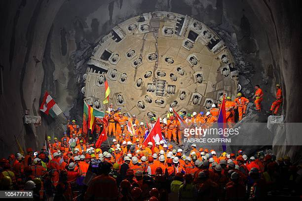 Miners hold national flags stand next to a giant drilling machine that completed the world's longest tunnel beneath the Swiss Alps during a ceremony...