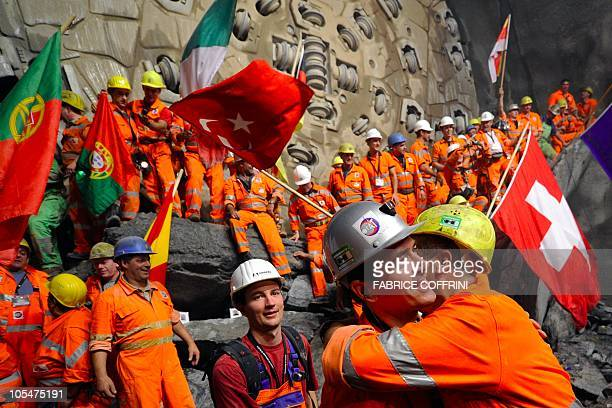 Miners hug after a giant drilling machine completed the world's longest tunnel beneath the Swiss Alps during a ceremony on October 15 30 kilometres...