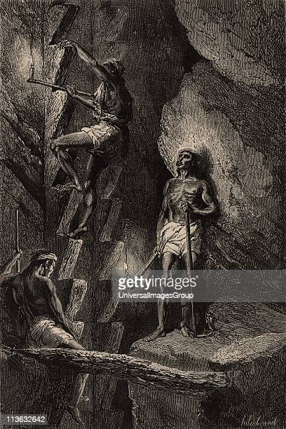 Miners in Chihuahua Mexico ascending a mineshaft by means of crude steps carrying candles attached to sticks to light their way Descending and...