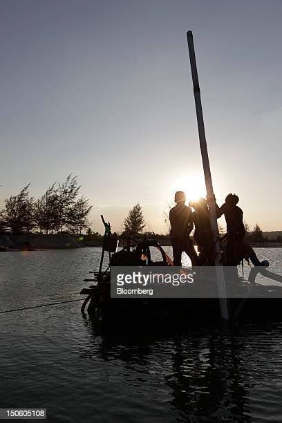 Miners operate a bamboo raft used to dredge for tin ore as the sun sets in Sungai Liat Bangka Island Indonesia on Friday July 27 2012 In recent years...
