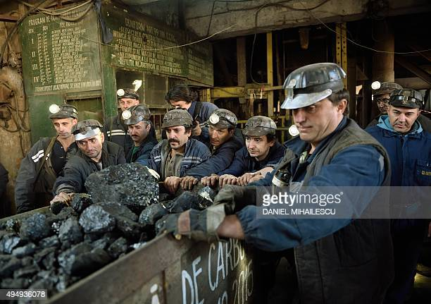 Miners push the last coal loaded mining carriage at the end of their last shift at the coal mine in the Romanian city of Petrila on October 30 2015...