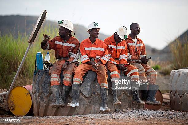 Miners sit on a rock above ground before returning to the digging face for their afternoon shift at the Gara gold mine operated by Randgold Resources...