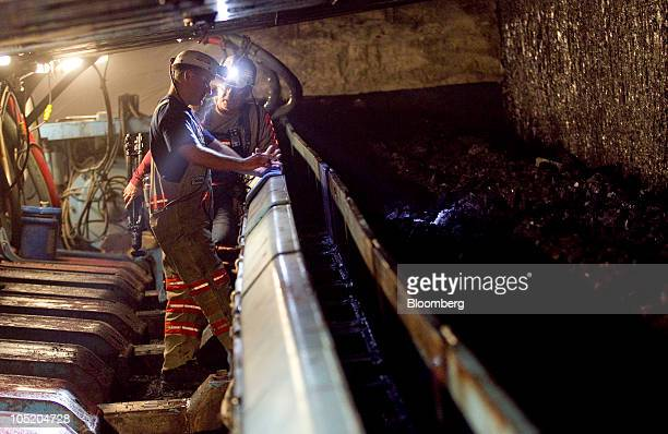 Miners talk next to the longwall coal seam in the Foresight Energy LLC's Pond Creek coal mine in Johnson City Illinois US on Monday June 21 2010 In...