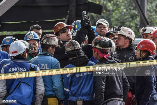 Miners talk to one of their bosses during search operations after an explosion at the El Cerezo illegal coal mine killed at least eight people in the...