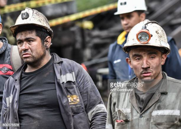Miners wait during search operations after an explosion at the El Cerezo illegal coal mine killed at least eight people in the rural area of Cucunuba...