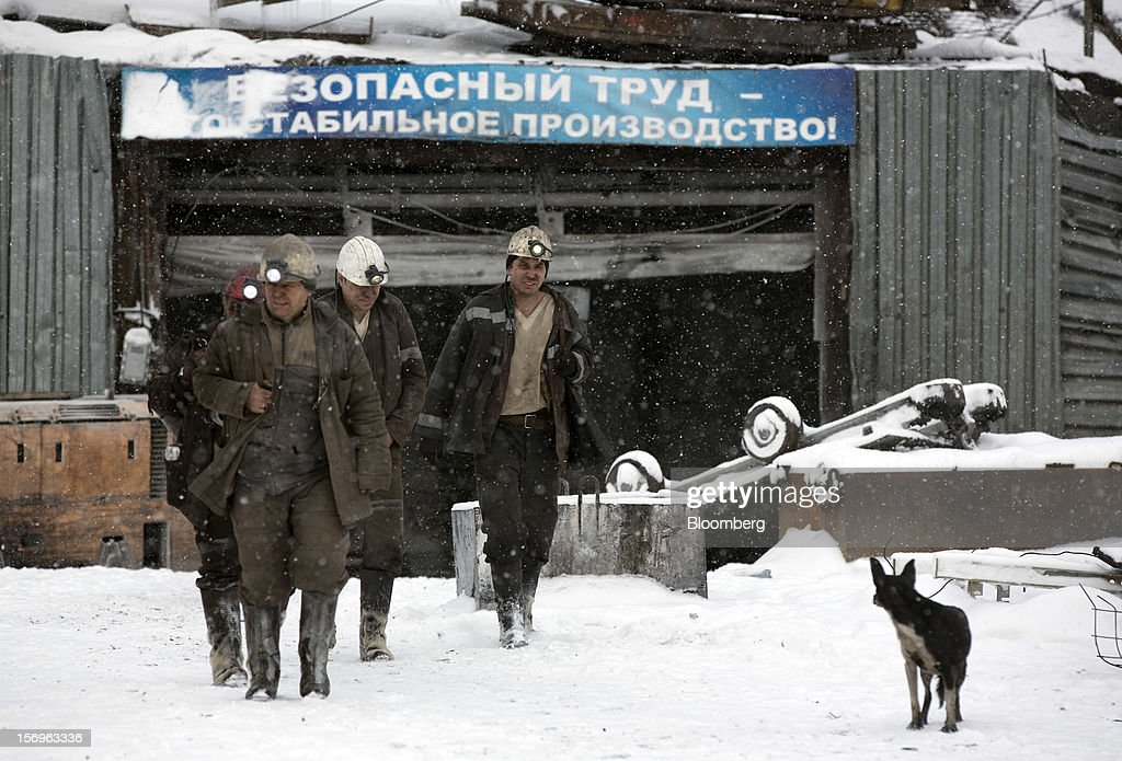 Miners walk through the snow after finishing their shift at the Sibirginsky open pit coal mine, owned by OAO Mechel and operated by Southern Kuzbass Coal Co., near Myski, in Kemerovo region of Siberia, Russia, on Friday, Nov. 23, 2012. OAO Mechel is Russia's biggest maker of steelmaking coal. Photographer: Andrey Rudakov/Bloomberg via Getty Images