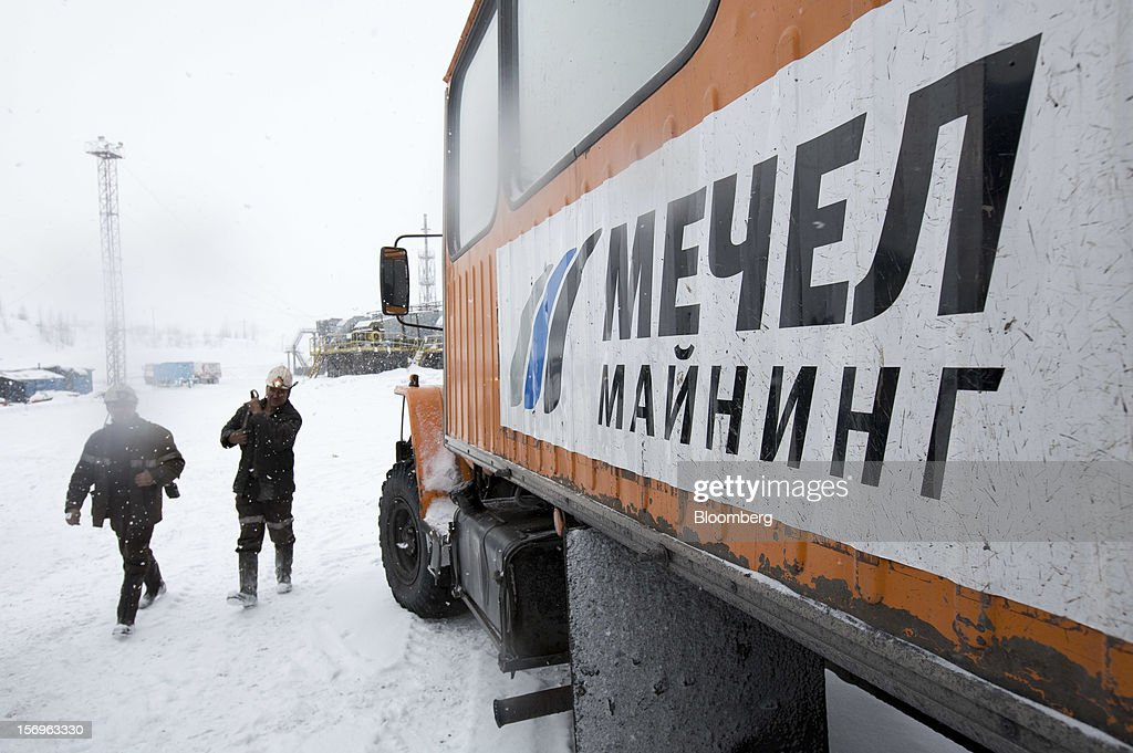 Miners walk through the snow past an OAO Mechel logo on the side of a transport bus after finishing their shift at the Sibirginsky open pit coal mine, owned by OAO Mechel and operated by Southern Kuzbass Coal Co., near Myski, in Kemerovo region of Siberia, Russia, on Friday, Nov. 23, 2012. OAO Mechel is Russia's biggest maker of steelmaking coal. Photographer: Andrey Rudakov/Bloomberg via Getty Images