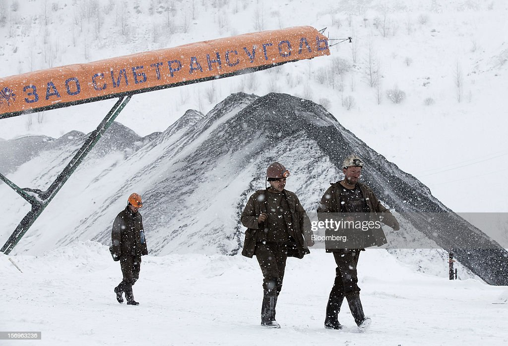 Miners walk through the snow past coal stores after finishing their shift at the Sibirginsky open pit coal mine, owned by OAO Mechel and operated by Southern Kuzbass Coal Co., near Myski, in Kemerovo region of Siberia, Russia, on Friday, Nov. 23, 2012. OAO Mechel is Russia's biggest maker of steelmaking coal. Photographer: Andrey Rudakov/Bloomberg via Getty Images