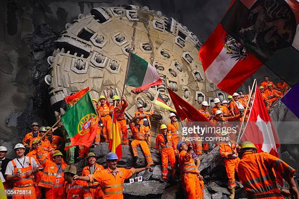 Miners wave as they celebrate after a giant drilling machine completed the world's longest tunnel beneath the Swiss Alps on October 15 30 kilometres...