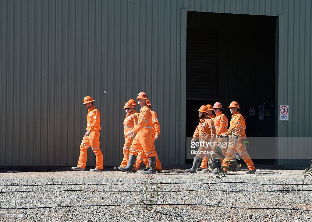 Miners wearing high-visibility overalls walk past a maintenance shed at the Sandfire Resources NL copper operations at DeGrussa, 559 miles (900 kilometers) north of Perth, Australia, on Sunday, Aug. 4, 2013. Copper, used in electrical wiring and tubes, is expected to gain until at least 2015, according to analyst forecasts compiled by Bloomberg, as aging ore bodies and few large new discoveries keep the metal's supply and demand balance tight. Photographer: Carla Gottgens/Bloomberg via Getty Images