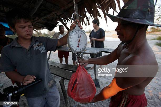 Miners weighs tin ore to be sold to a buyer in Sungai Liat Bangka Island Indonesia on Friday July 27 2012 In recent years about onethird of all the...