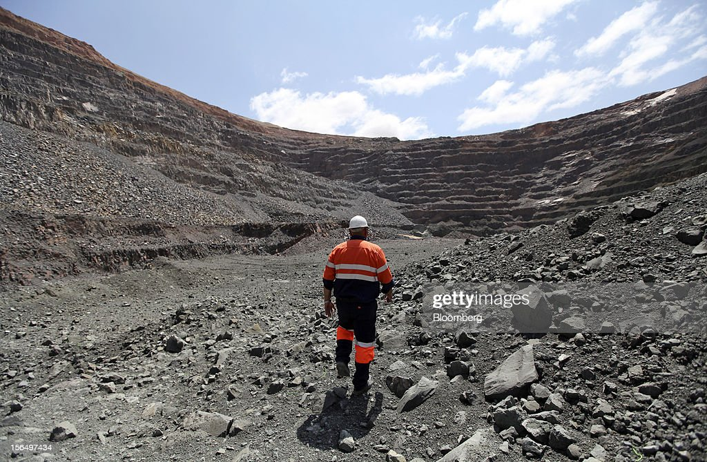 A mineworker walks across diamond-bearing kimberlite rock on the pit floor of the Jwaneng mine, operated by the Debswana Diamond Co., a joint venture between De Beers and Botswana's government, in Jwaneng, Botswana, on Wednesday, Oct. 24, 2012. De Beers, the biggest diamond producer by revenue, is moving the sorting and trading of rough stones to Botswana from London to secure access to the world's largest supplier of diamonds by value and challenge Antwerp's dominance as the world's biggest trading hub for rough diamonds. Photographer: Chris Ratcliffe/Bloomberg via Getty Images