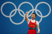 Mingjuan Wang of China celebrates after a lift in the Women's 48kg Group A weightlifting on Day 1 of the London 2012 Olympic Games at ExCeL on July...