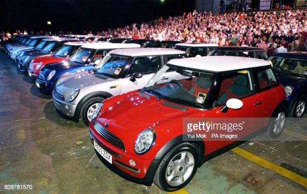 Mini cars are linedup in front of a crowd of employees gathered to watch a special screening of the new film 'The Italian Job' on a giant screen at...