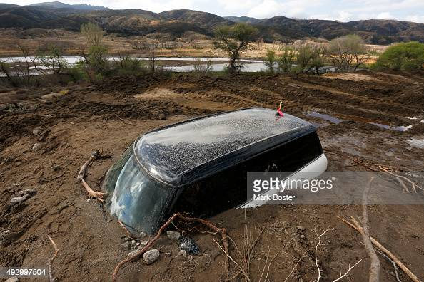 Mini Cooper buried up to thw windows is one of Several cars on Elizabeth Lake Road left inundated with mud after a deluge Thursday caused mudslides...