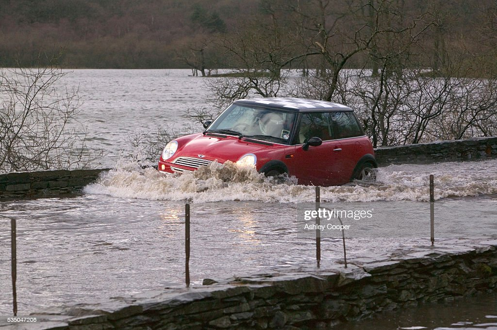 A mini drives through flood water at rydal after a severe storm Rydal Cumbria