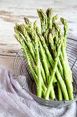 Mini organic green asparagus in a wire basket