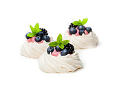 Mini  Pavlova meringue nests with berries and mint isolated on white