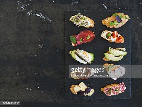 Mini sandwich set. Variety of small sandwiches on black backdrop : Stock Photo