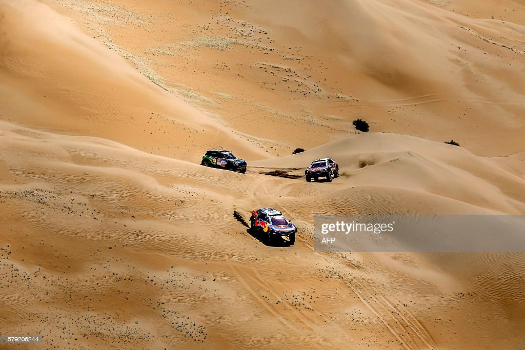 TOPSHOT Mini team's Yazeed Mohamed alRhaji trails Peugeot team's Stephane Peterhansel and Cyril Despres during the 14th special stage of the Silkway...