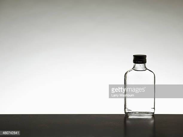 A miniature bottle of alcohol without a label, back lit