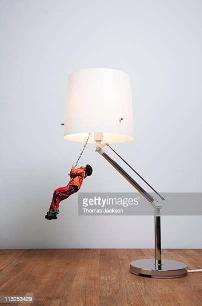 Miniature boy swinging from lamp