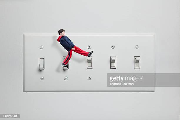 Miniature boy walking on light switches