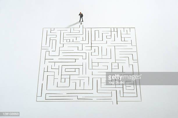 Miniature businessman ponder the maze