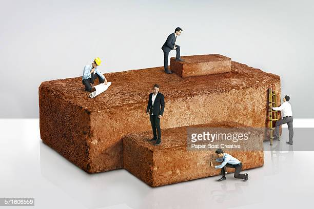 Miniature businessmen putting bricks together