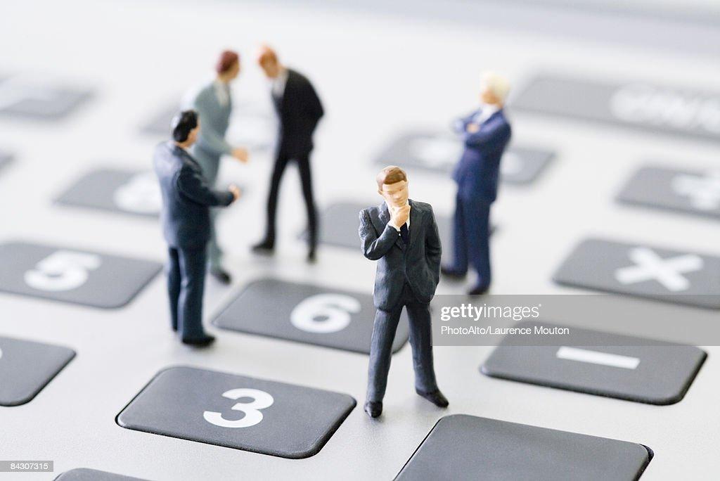 Miniature businessmen standing on calculator