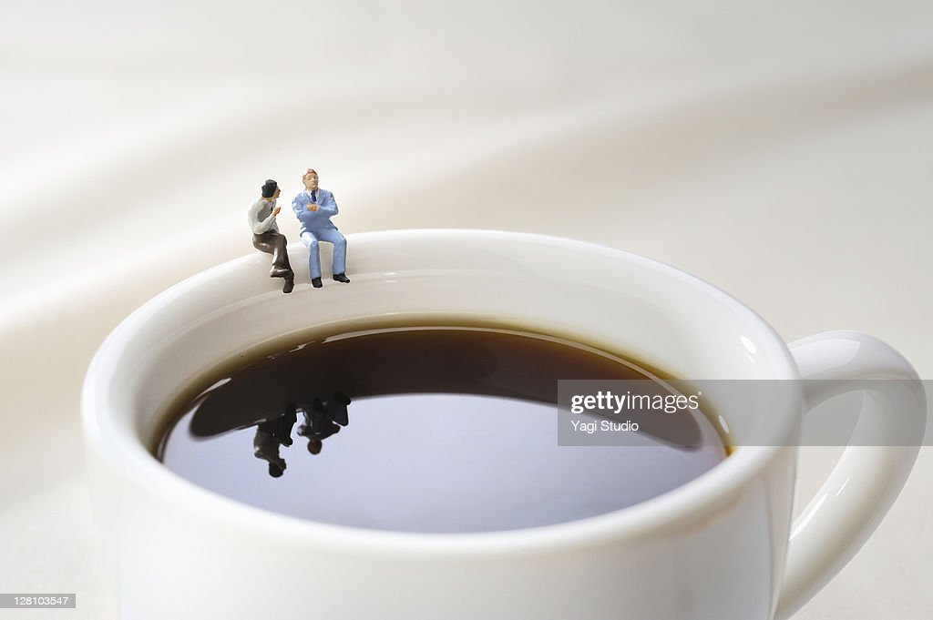 Miniature doll sat chatting on a cup