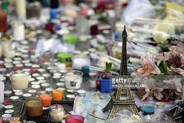 A miniature Eiffel tower candles and flowers are seen at a makeshift memorial outside 'Le Carillon cafe' at the corner of Rue Bichat and Alibert in...