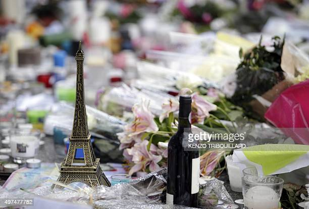 A miniature Eiffel tower candles flowers and a bottle of red wine are seen at a makeshift memorial outside 'Le Carillon cafe' at the corner of Rue...