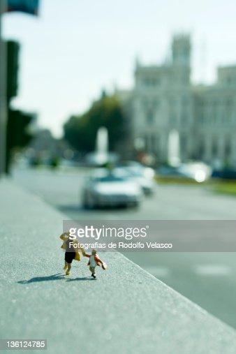Miniature figures running around city : Stock Photo