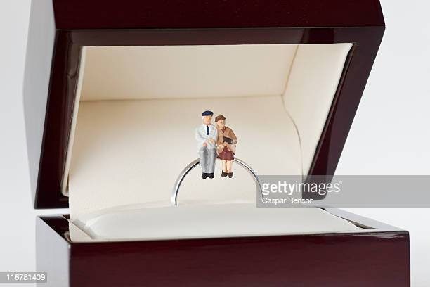 Miniature figurines of a senior woman and senior man sitting together on a wedding ring