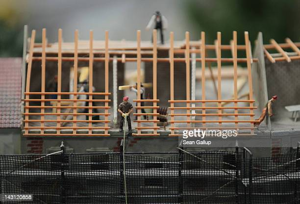 Miniature figurines of construction workers rebuild an apartment building roof at the LOXX miniature train landscape at the Alexa shopping mall on...