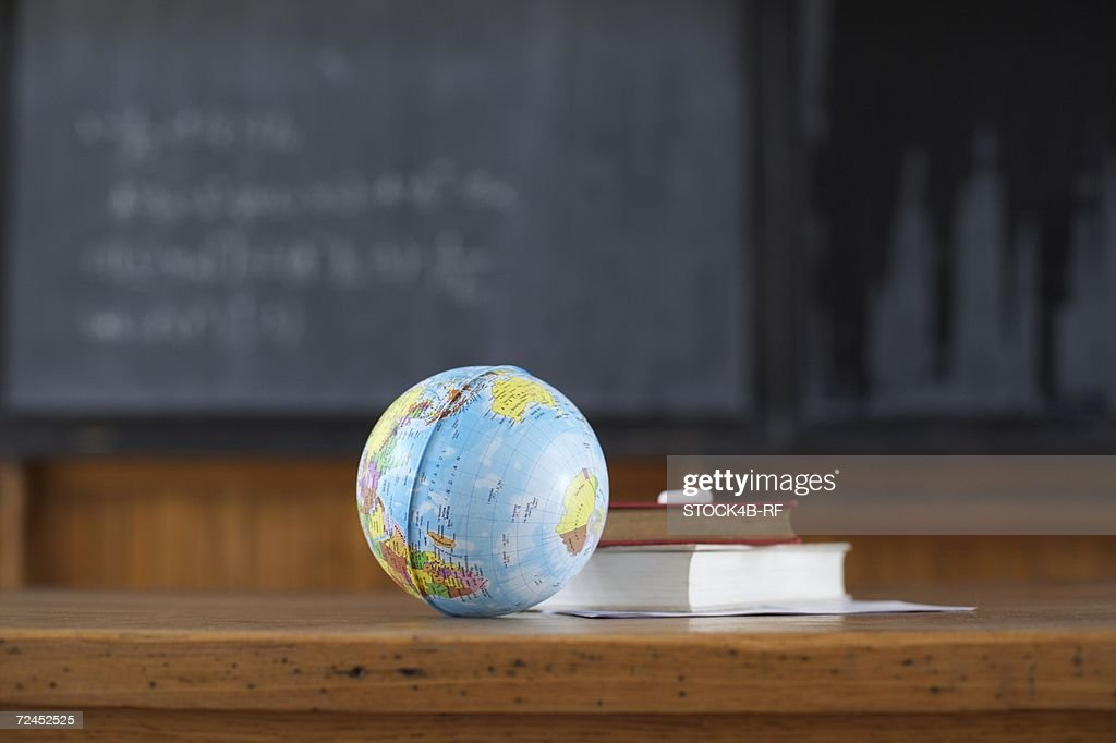 Miniature globe and book on a desk in front of a blackboard, selective focus : Stock Photo