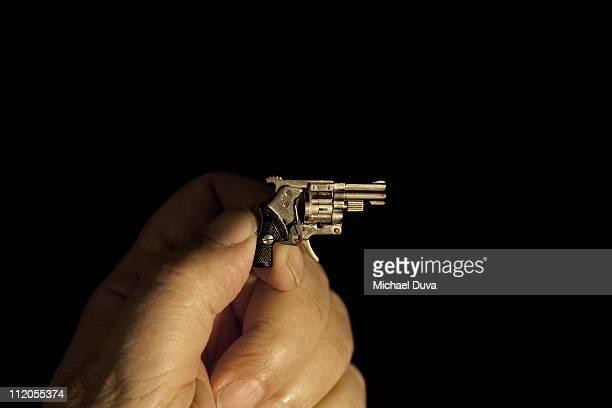 miniature gun in hand on black background