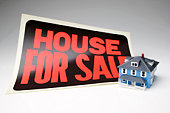 Miniature house and for sale sign