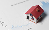 High quality 3d render of a miniature house on a blue financial chart. Housing market concept. Miniature house is lit by the upper left corner of composition. Horizontal composition with copy space. G